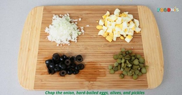 Chop the onion, hard-boiled eggs, olives, and pickles